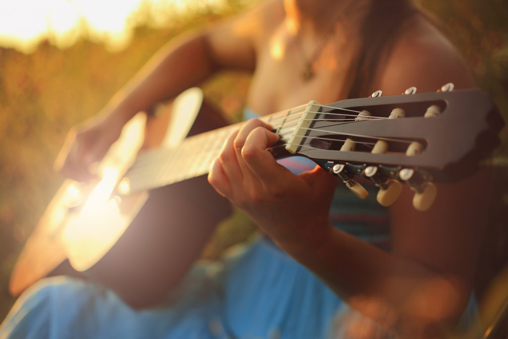 Beautiful woman playing the acoustic guitar in field