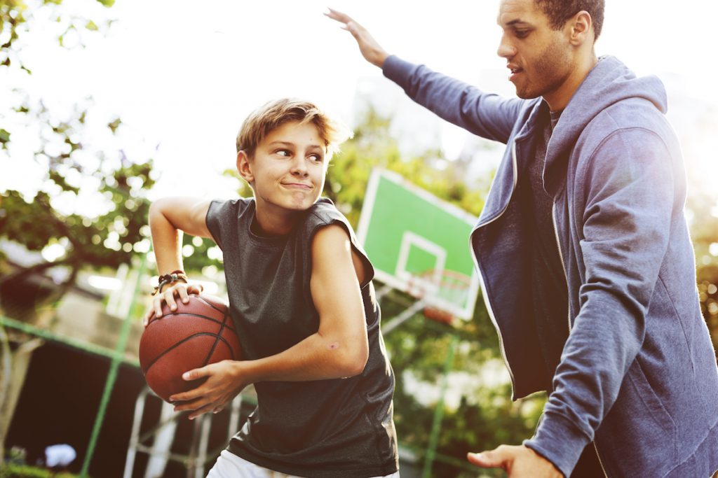 Teenager practing is basketball with his coach